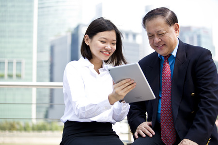 real leader: Asian businessman and young female executive using tablet Stock Photo