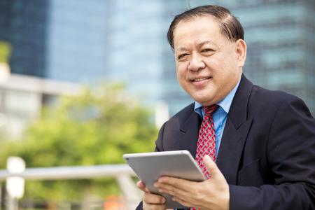 real leader: Asian businessman using tablet