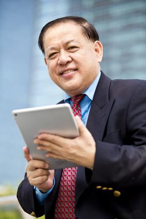 D'affaires asiatique en utilisant la tablette