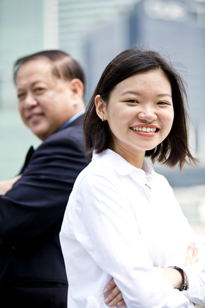 real leader: Asian businessman and young female executive smiling portrait Stock Photo