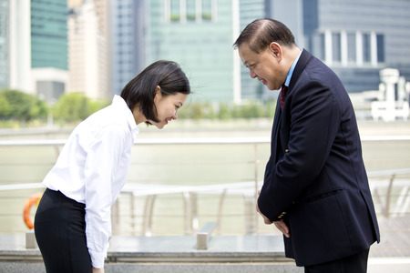 Asian businessman and young female executive bowing Stok Fotoğraf