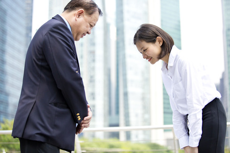 Asian businessman and young female executive bowing Banque d'images