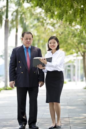 real leader: Asian businessman and young female executive walking together