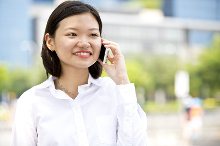 Asian young female executive talking on smart phone photo