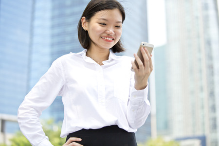Asian young female executive looking at smart phone photo