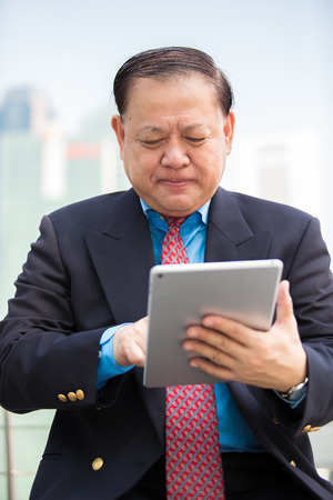 real leader: Senior Asian businessman in suit using tablet PC