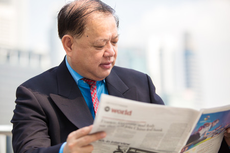 real leader: Senior Asian businessman in suit reading newspaper Stock Photo
