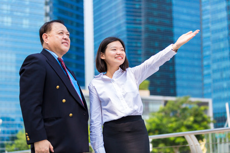 real leader: Senior businessman and young female executive pointing at a direction