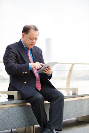 D'affaires asiatique en costume principal en utilisant la tablette PC