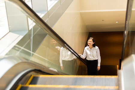Young Asian female executive going up escalator