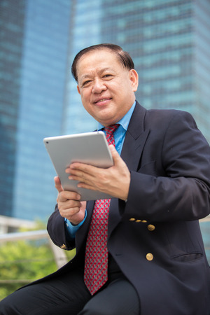 Senior Asian businessman in suit using tablet PC