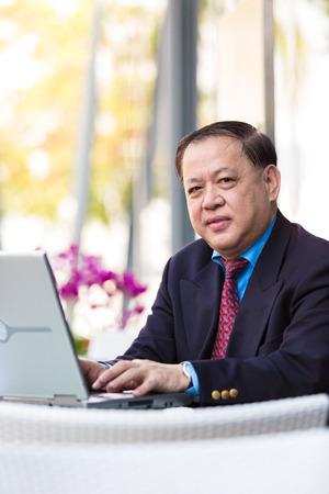 D'affaires asiatique en costume senior utilisant un ordinateur portable PC