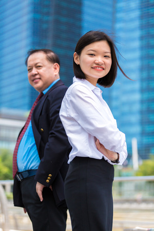 Young Asian female executive and senior businessman in suit portrait Stock Photo