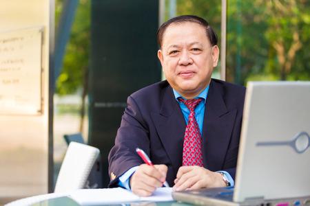 Senior Asian businessman in suit writing proposal