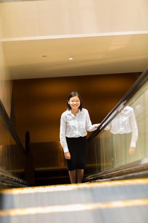 Young Asian female executive going up escalator