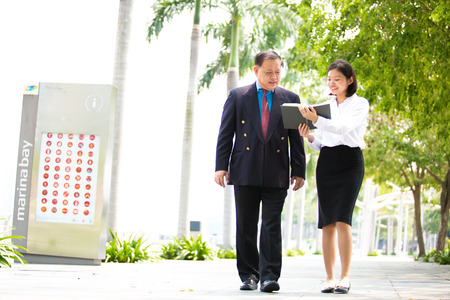 Young Asian female executive and senior businessman walking together