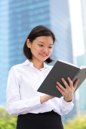 Young Asian female executive reading book smiling portrait