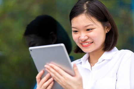 Young Asian female executive using tablet PC Stock Photo