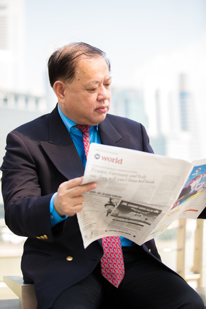 Senior Asian businessman in suit reading newspaper Stock Photo