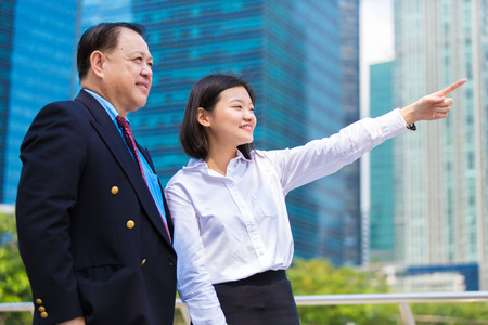 Senior businessman and young female executive pointing at a direction