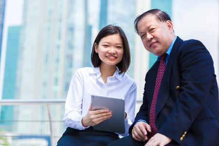 Jeune ex�cutif femme asiatique et homme d'affaires sup�rieurs � l'aide tablette PC