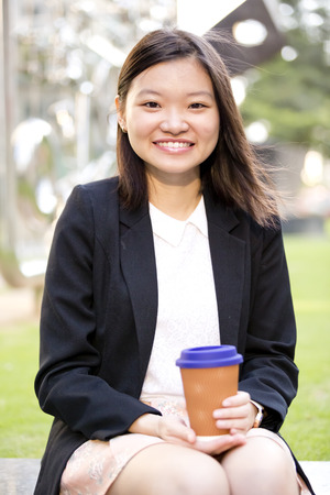 Young Asian female executive drinking coffee Stock Photo