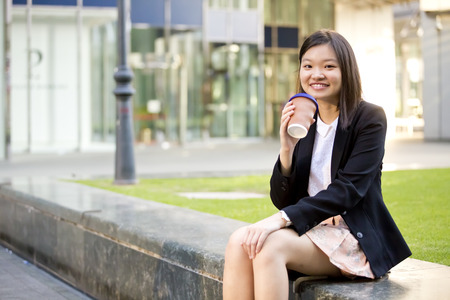 Young Asian female executive drinking coffee and reading newspaper Stock Photo