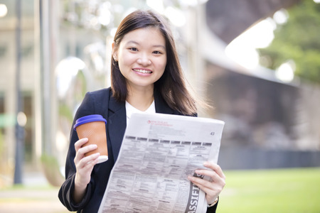 real leader: Young Asian female executive drinking coffee and reading newspaper Stock Photo