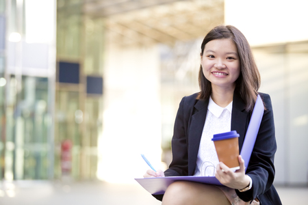real leader: Young Asian female executive drinking coffee and holding file
