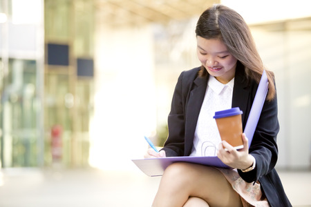 Young Asian female executive drinking coffee and holding file