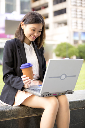 Young Asian female executive drinking coffee and using laptop PC