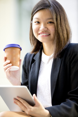 Young Asian female executive drinking coffee and using tablet PC