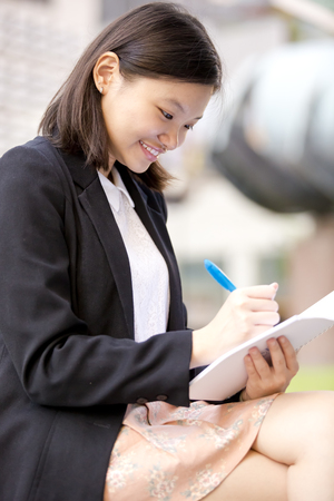 Young Asian female executive writing on notepad