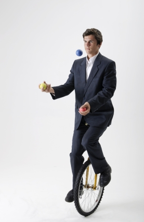 juggling: Businessman riding a unicycle while juggling three colored balls