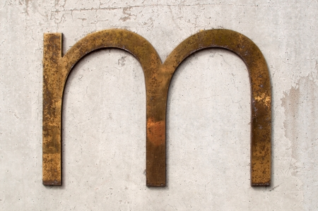 tarnished: A dirty and tarnished metallic letter m on a grey concrete wall Stock Photo
