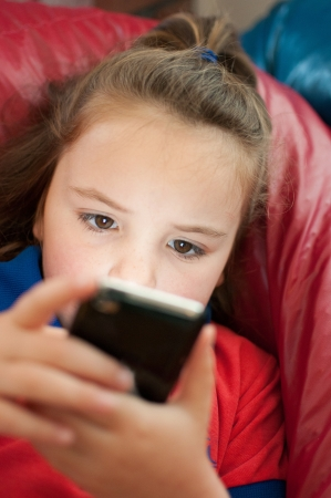 beanbag: A young girl sits on a red beanbag while playing a game on a mobile phone