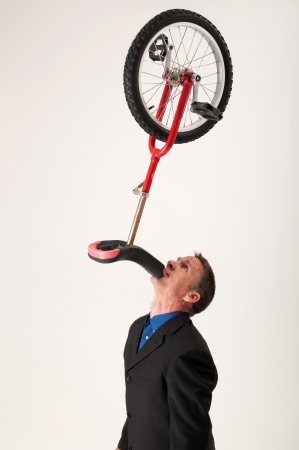 A handsome businessman balances a red unicycle on his chin photo