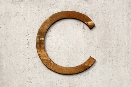 tarnished: A dirty and tarnished metallic letter c on a gray concrete wall