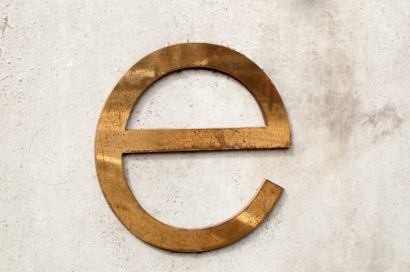 tarnished: A dirty and tarnished metallic letter e on a gray concrete wall Stock Photo