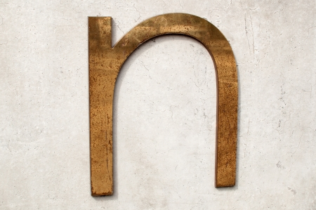 tarnished: A dirty and tarnished metallic letter n on a gray concrete wall