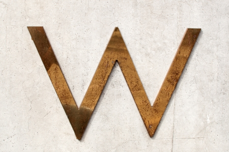 tarnished: A dirty and tarnished metallic letter w on a gray concrete wall