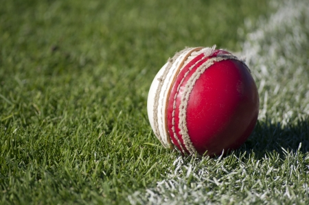 cricket ball: An old red and white cricket ball with worn stitching sits abandoned on the sports field boundary