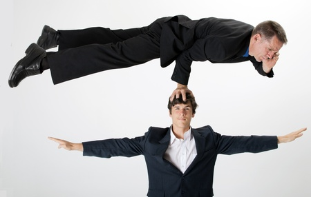 A businessman talks on his mobile telephone while balancing with one arm on the head of a colleague photo