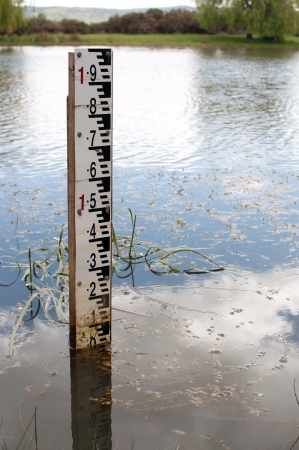 depth measurement: A guage to measure the depth of a flooded river Stock Photo