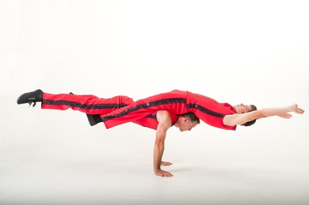 requiring: Two acrobats in red costumes balance in a pose requiring teamwork and strength