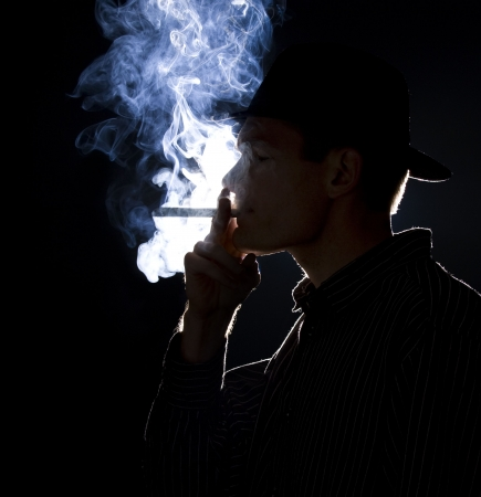 mobster: Backlit man smoking a cigar or cigarette with lots of smoke visible