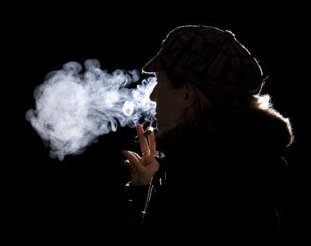 women smoking: Using rim light to show young woman smoking with hat