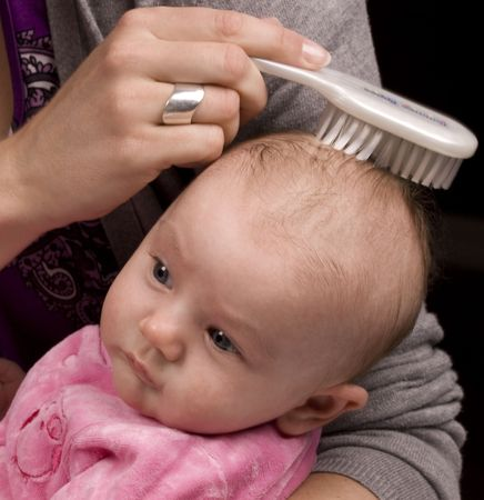 Mother brushing her daughter 's hair with a white brush. Stock Photo