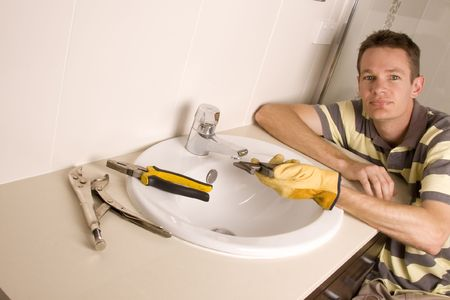 Plumber working on a broken tap in a bathroom sink photo