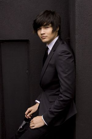 Young model in a black suit against a black wall